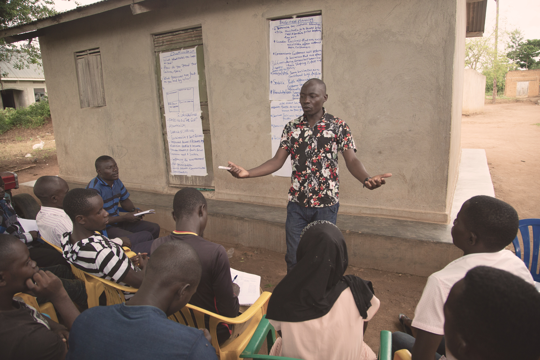 A young man in a Hawaiian shirt addresses members of the East Africa Youth Inclusion Project, who sit in plastic chairs in front of a small building with big pieces of paper taped to it that has notes about business development.