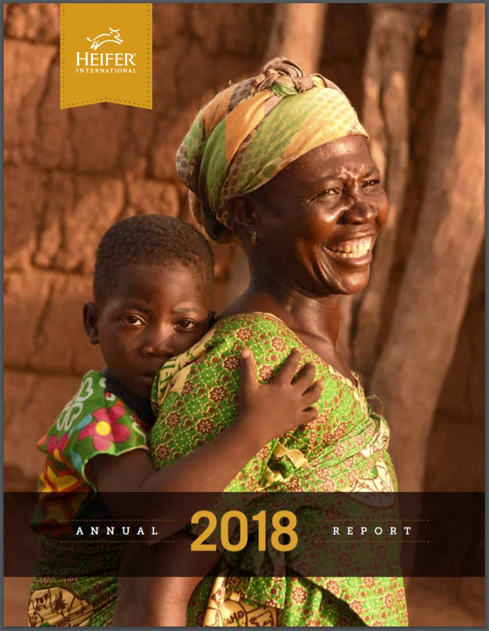 """A woman with a big smile carries a child on her back. The bottom of the photo says, """"2018: Annual Report."""""""