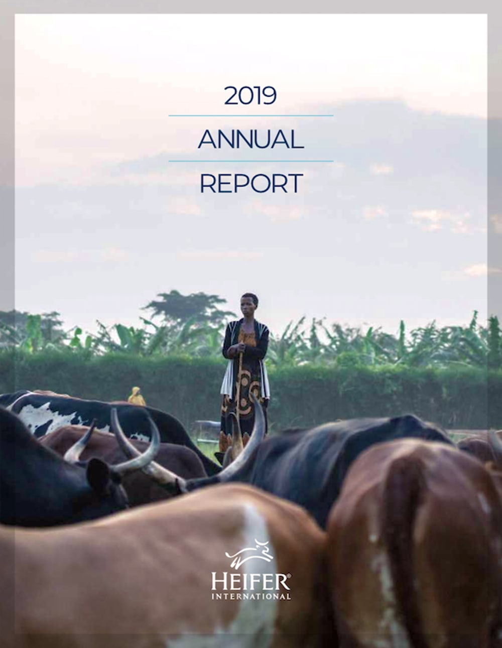 "A woman watches over her cattle herd. The top of the photo says, ""2019: Annual Report."""