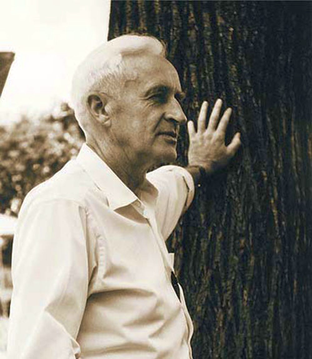 Historical photo of Dan West leaning on a tree.