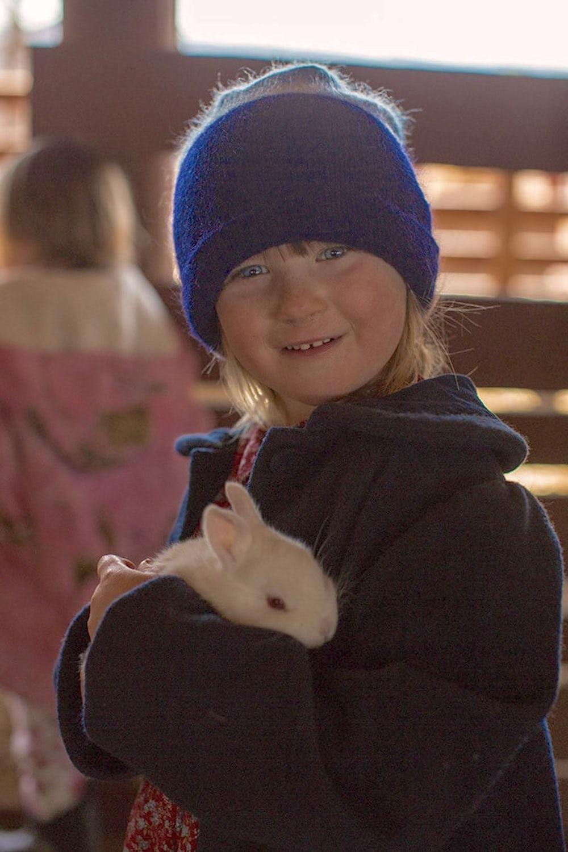 Child holds hope basket rabbit