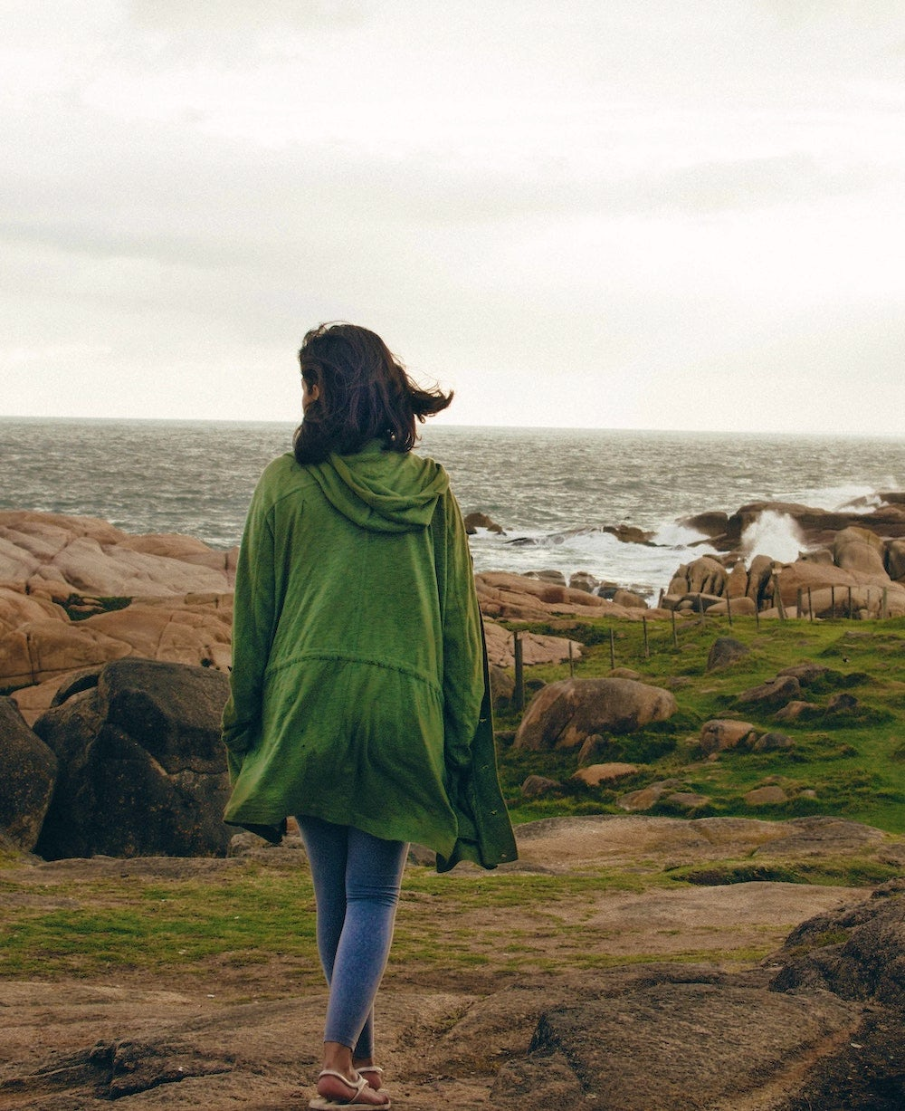 A woman takes a walk on a rocky beach in a green jacket.