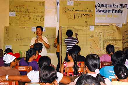 People in the village of Angas gather for a CMDDR workshop with HEED.