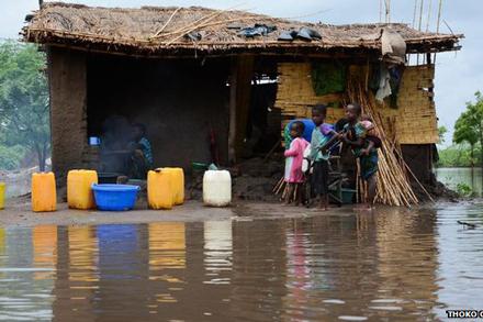 Children stand near damaged house in Malawi