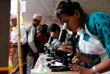 techs look through microscopes