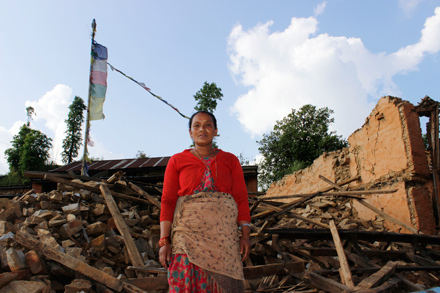 A woman stands in front of her home that collapsed in the April 25 earthquake that struck Nepal.