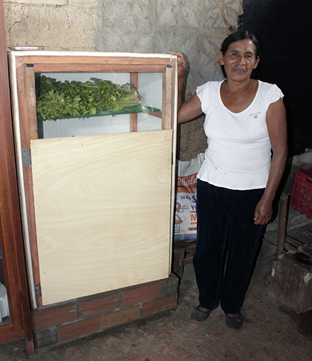 Ines stands with her ecological refrigerator. The refrigerator, which Yours learned how to build during Heifer trainings, enable her to plan meals and keep her garden vegetable fresh longer.