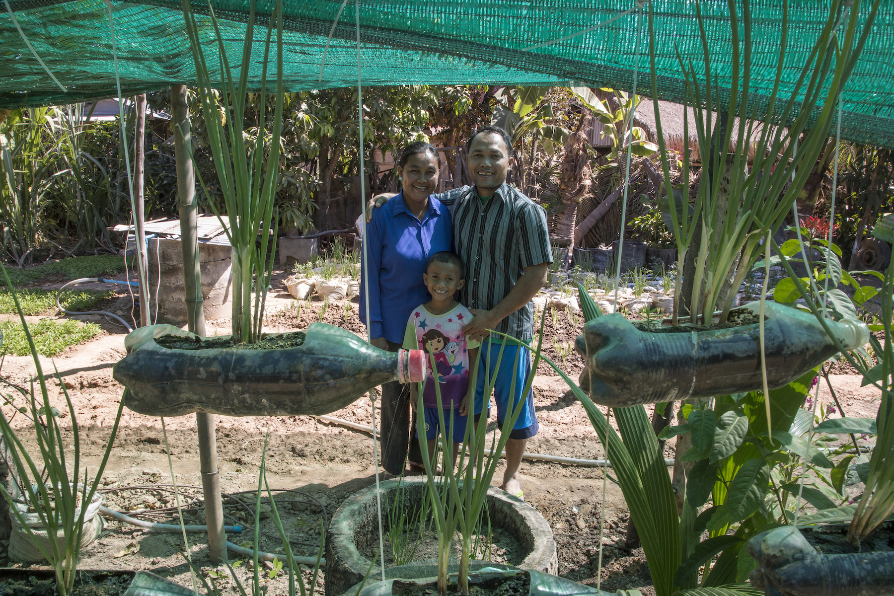 Klang Savuth, Kid Moa and Ky Damkoeung, their youngest of two sons, stand in front of their garden in Kok Komeat, Cambodia. Photo by Omar Havana.