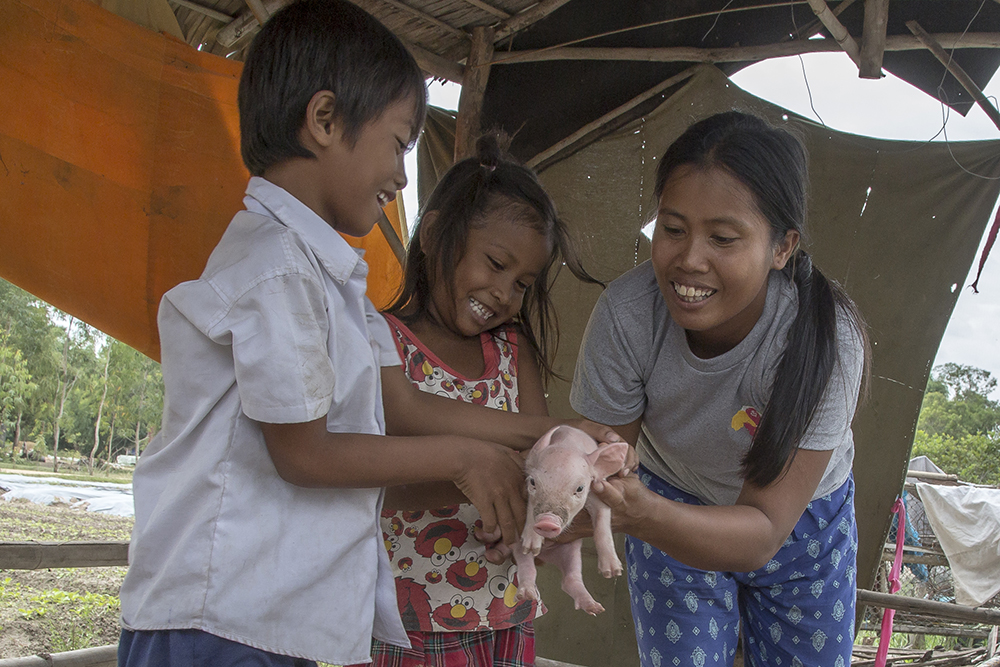 Ou Kongkea (29) (right) shows her children, Vatu Samady (7) (left) and Vatu Somavatey (5) (center), how to hold a piglet inside a pig sty set up outside the family home on December 05, 2015, in Svay Thom, Cambodia.