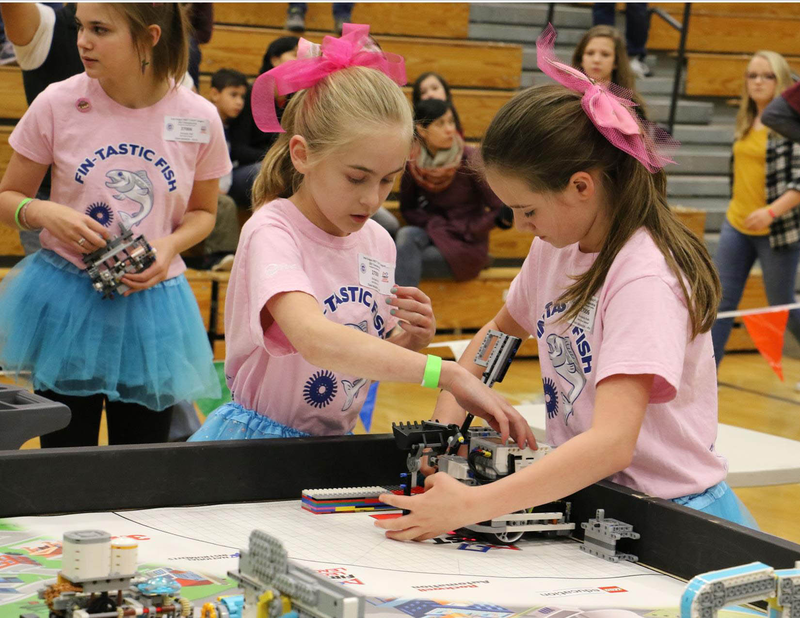 The girls' robotics team works on their project.