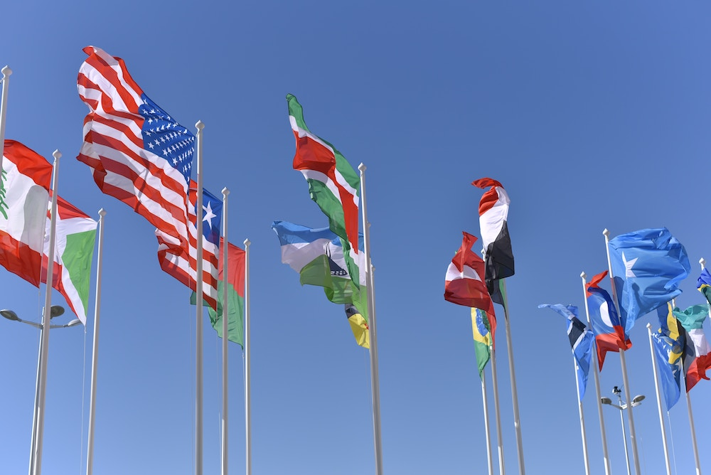 International flags flying in a blue sky.