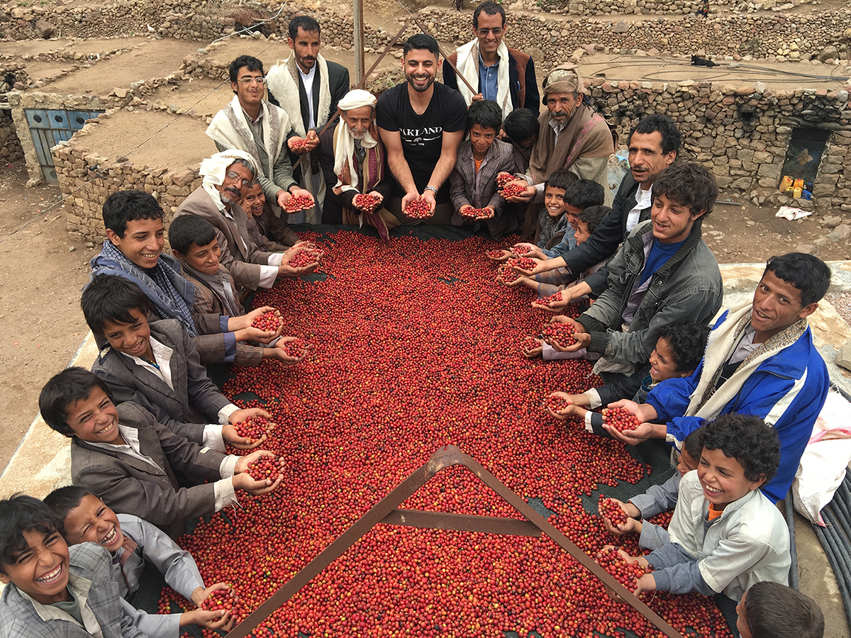 Alkanshali laughing with a coffee-producing community around a drying bed.