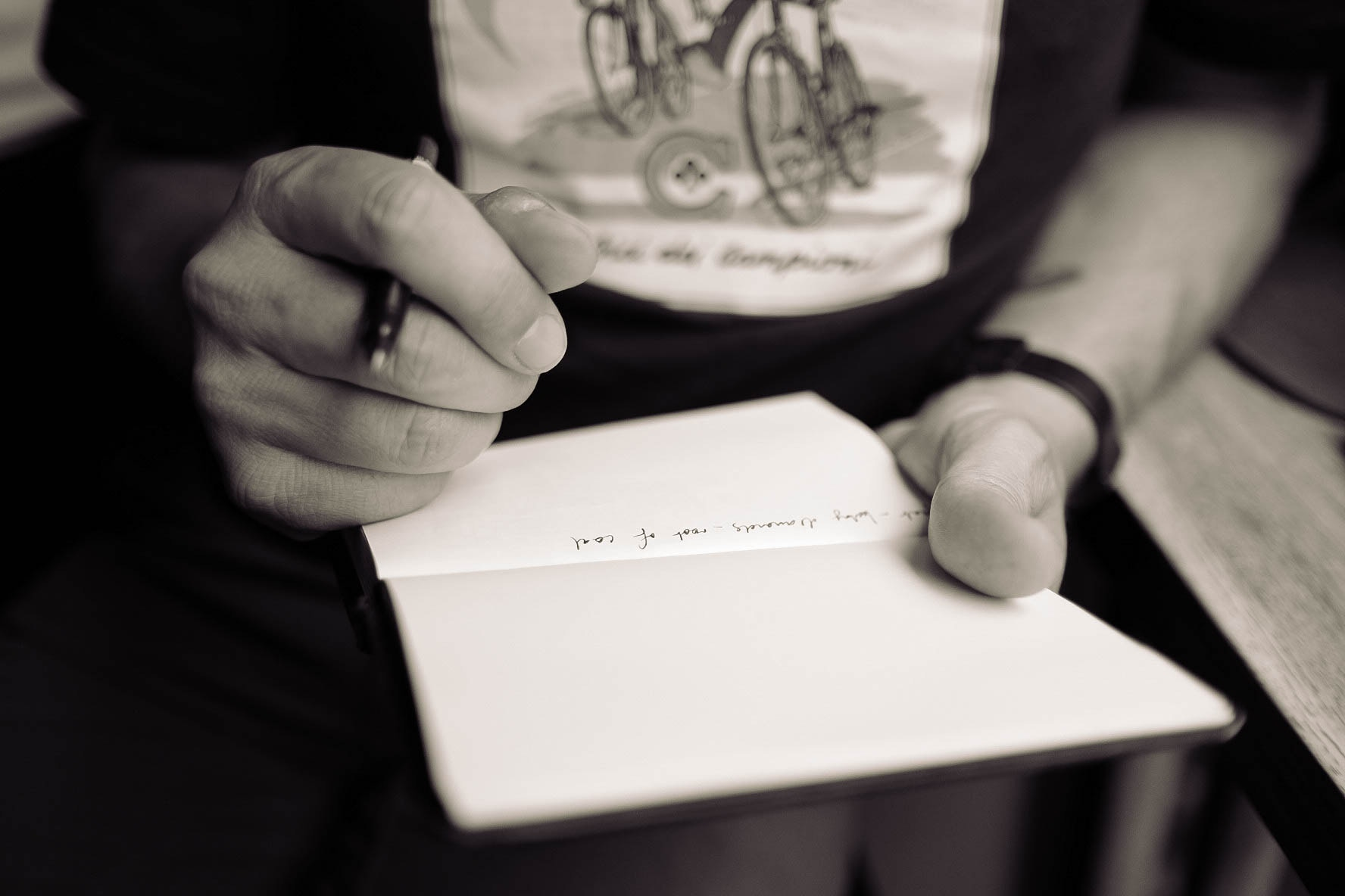 A woman's hands writing in a notebook.
