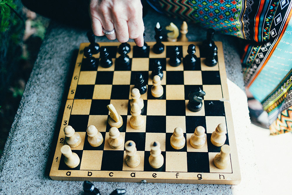 A chess board with a woman's hand moving a piece.