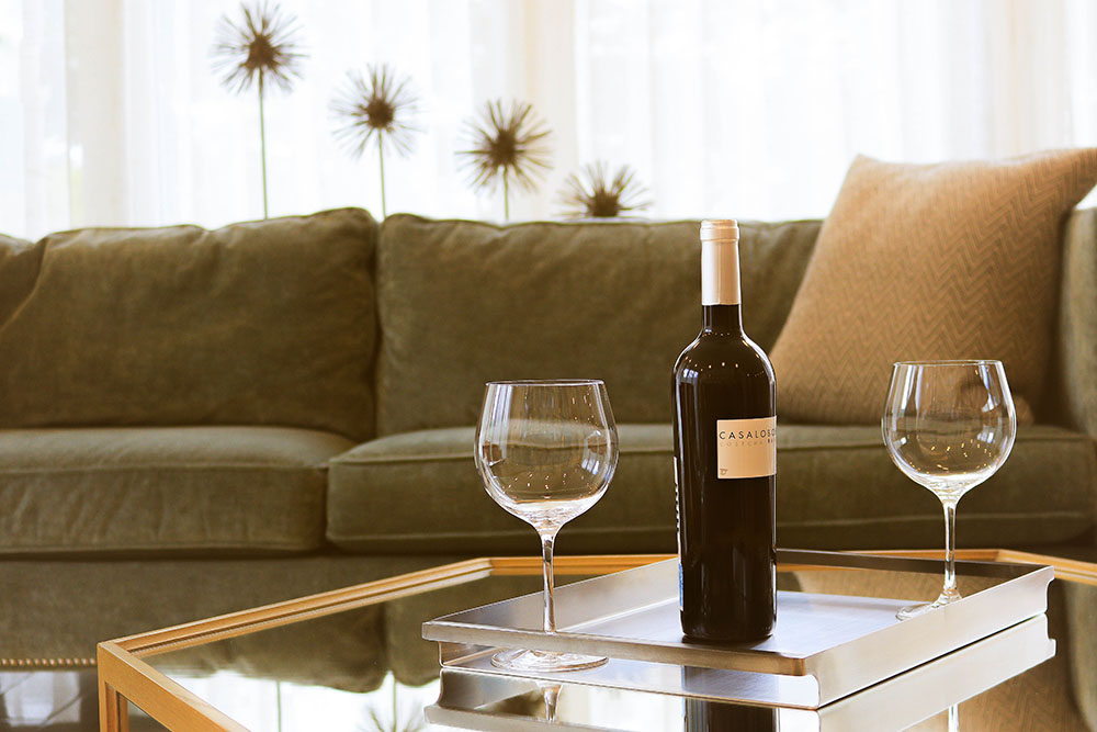 A couch with two wine glasses on a table.