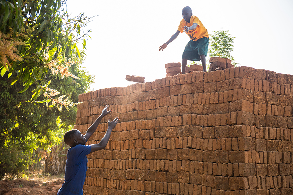 Ojok Ivan Emmanuel, 17, and his brother Ronnie Owekgiu, 12, work together to pile up clay bricks.