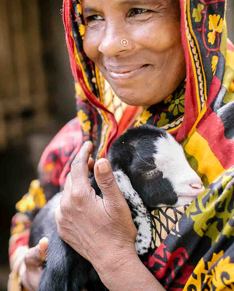 Monoara Begum cuddles one of her baby goats.