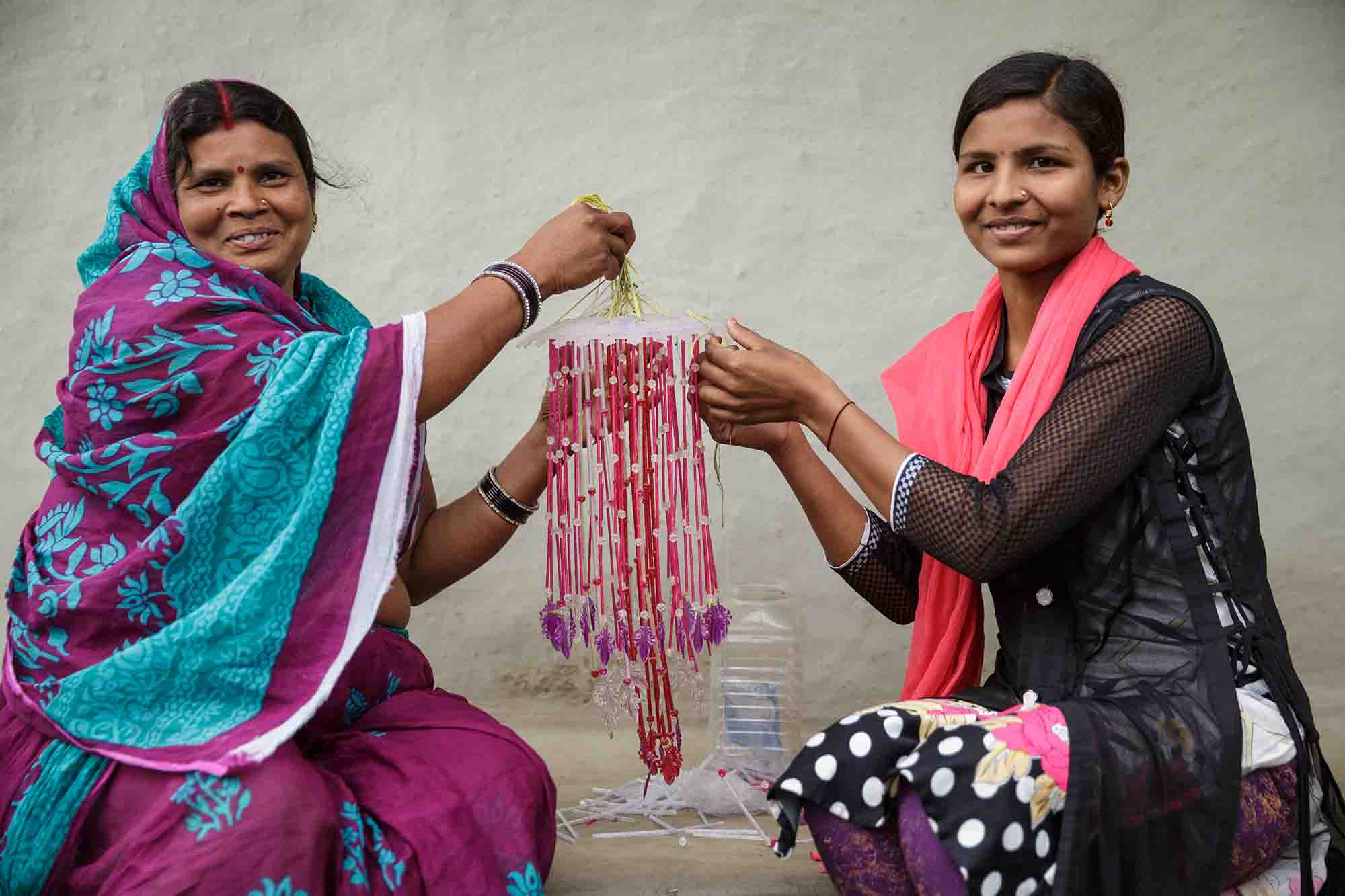 Munni Devi and her daughter Preeti Kumar, 19, make a wind chime together.