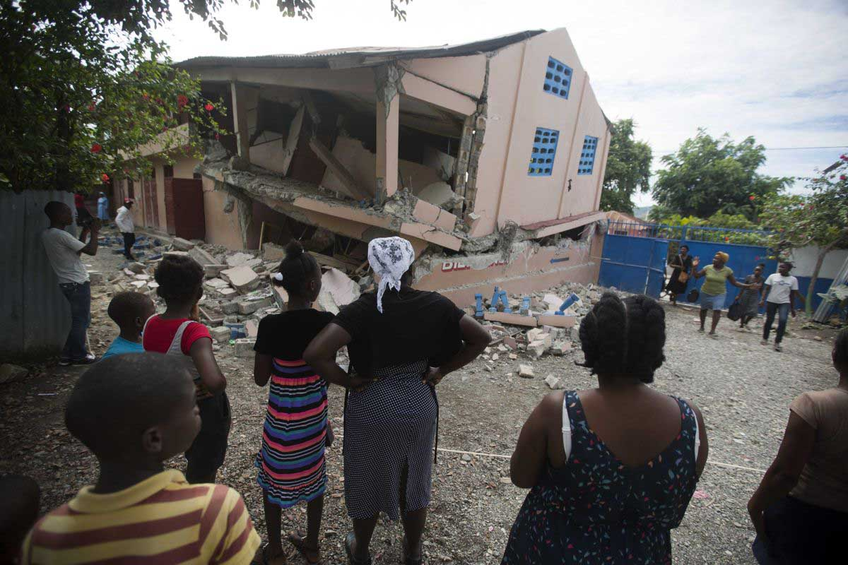 Haitians look at damage caused from a 5.9 magnitude earthquake. AP Photo Dieu Nalio Chery