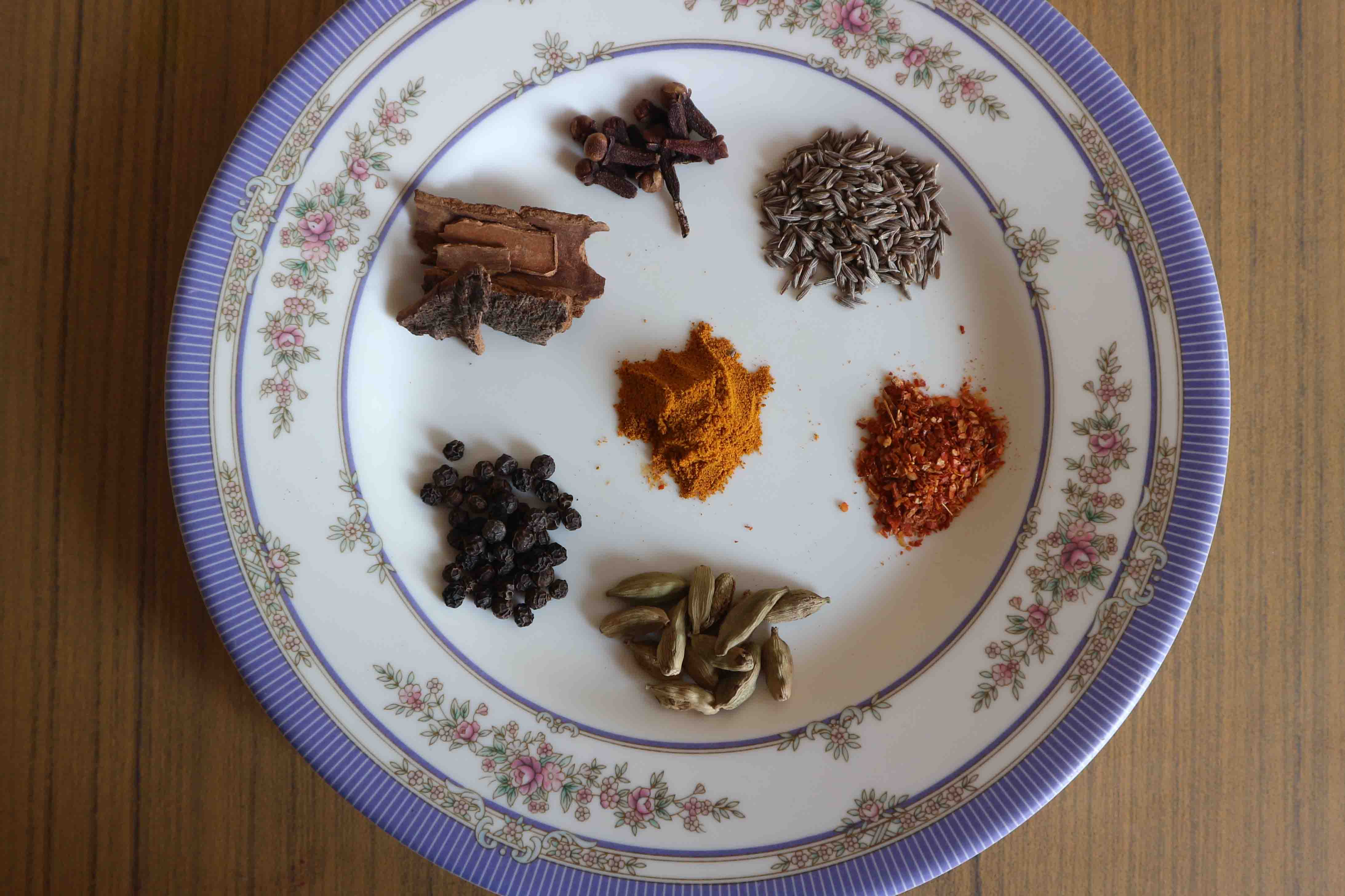 Spices for the curry include cumin, tumeric, cinnamon, cardamom, black pepper, cloves and red chili flakes.