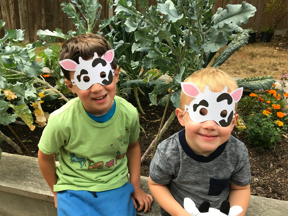 Two boys wear cow masks.