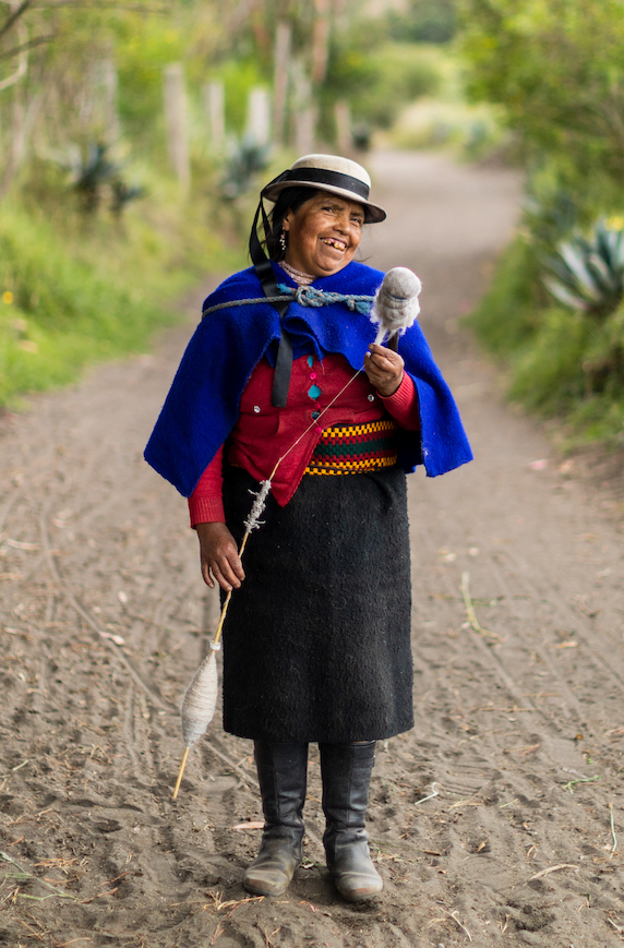 María Micaela Castro Sisa poses wearing a traditional Quechua outfit including a blue poncho, multicolored wide belt and black skirt.