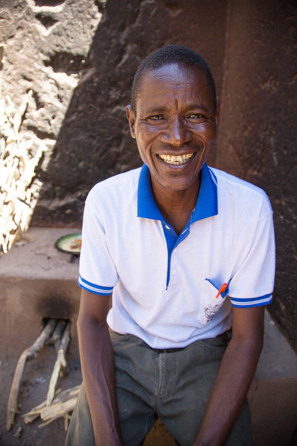 Socha sits smiling on the improved stove he built for Stella.