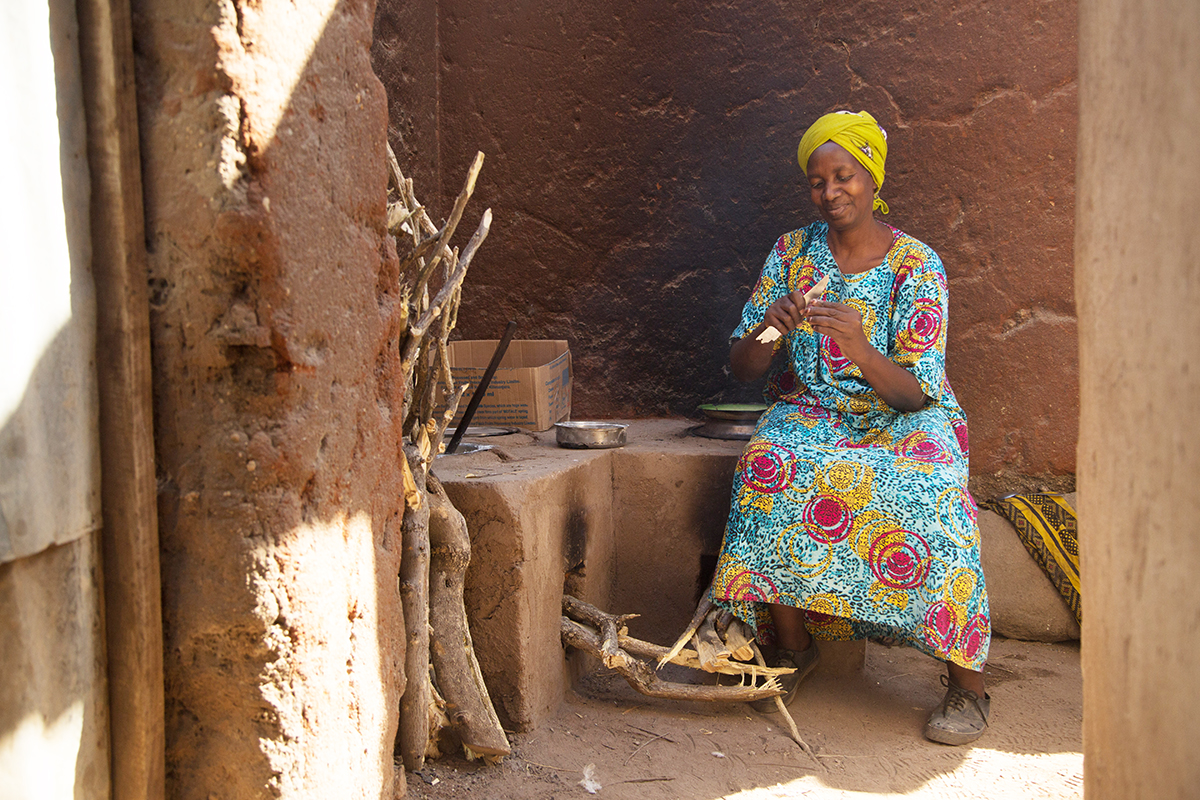 Stella sits near her stove preparing onions for a meal.