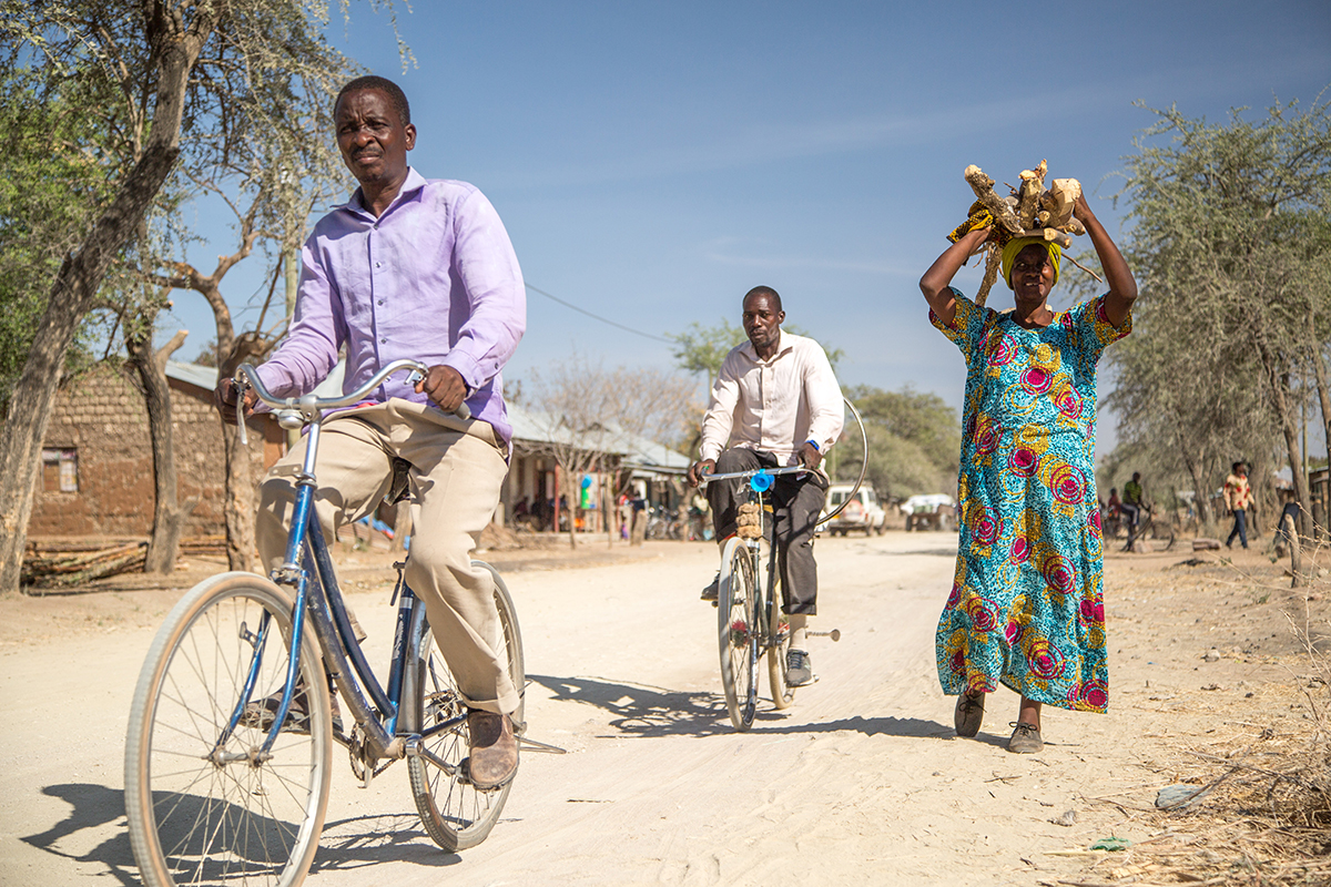 Socha and another man ride bicycles through the village, while Stella walks carrying items above her head.