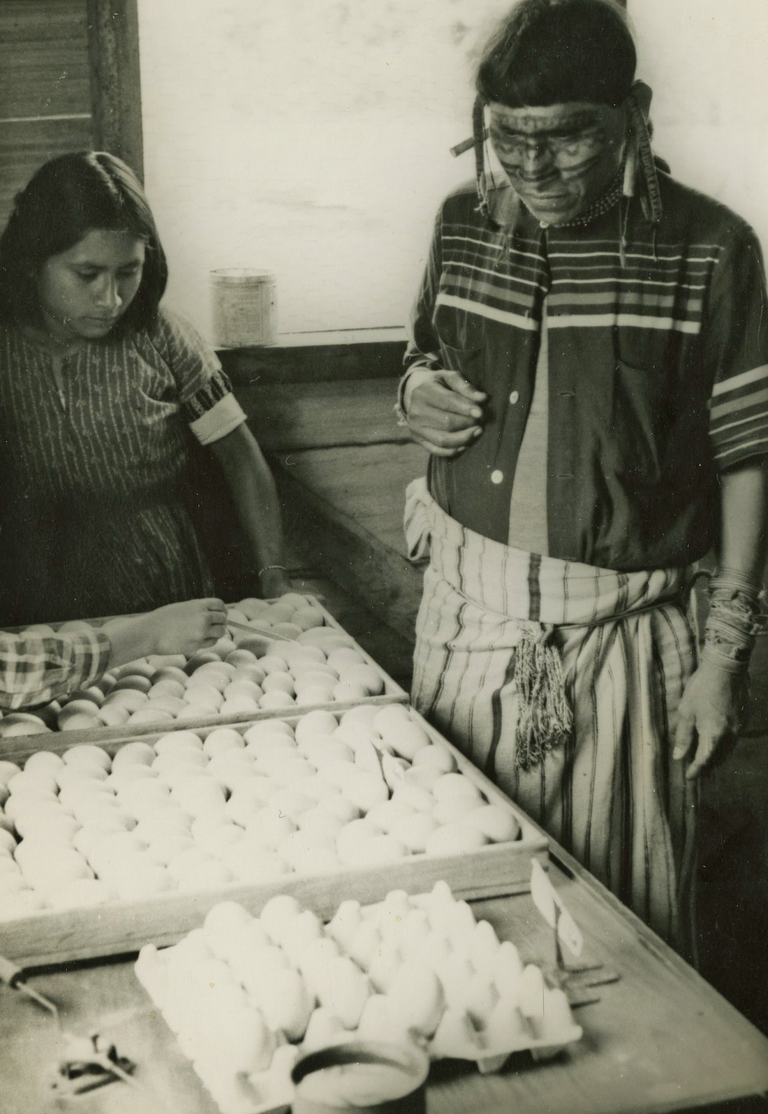 Two native Bolivians examine a crate of eggs.