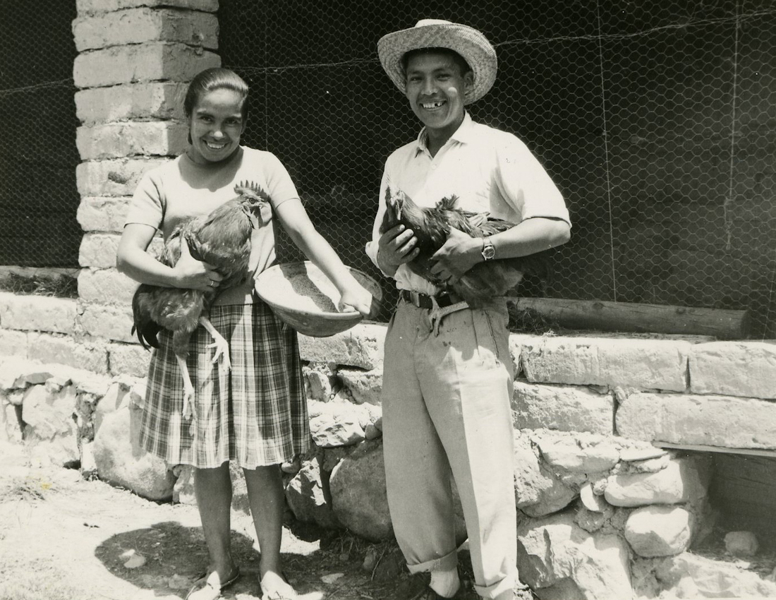 A native Bolivian man and woman smile while they hold chickens.