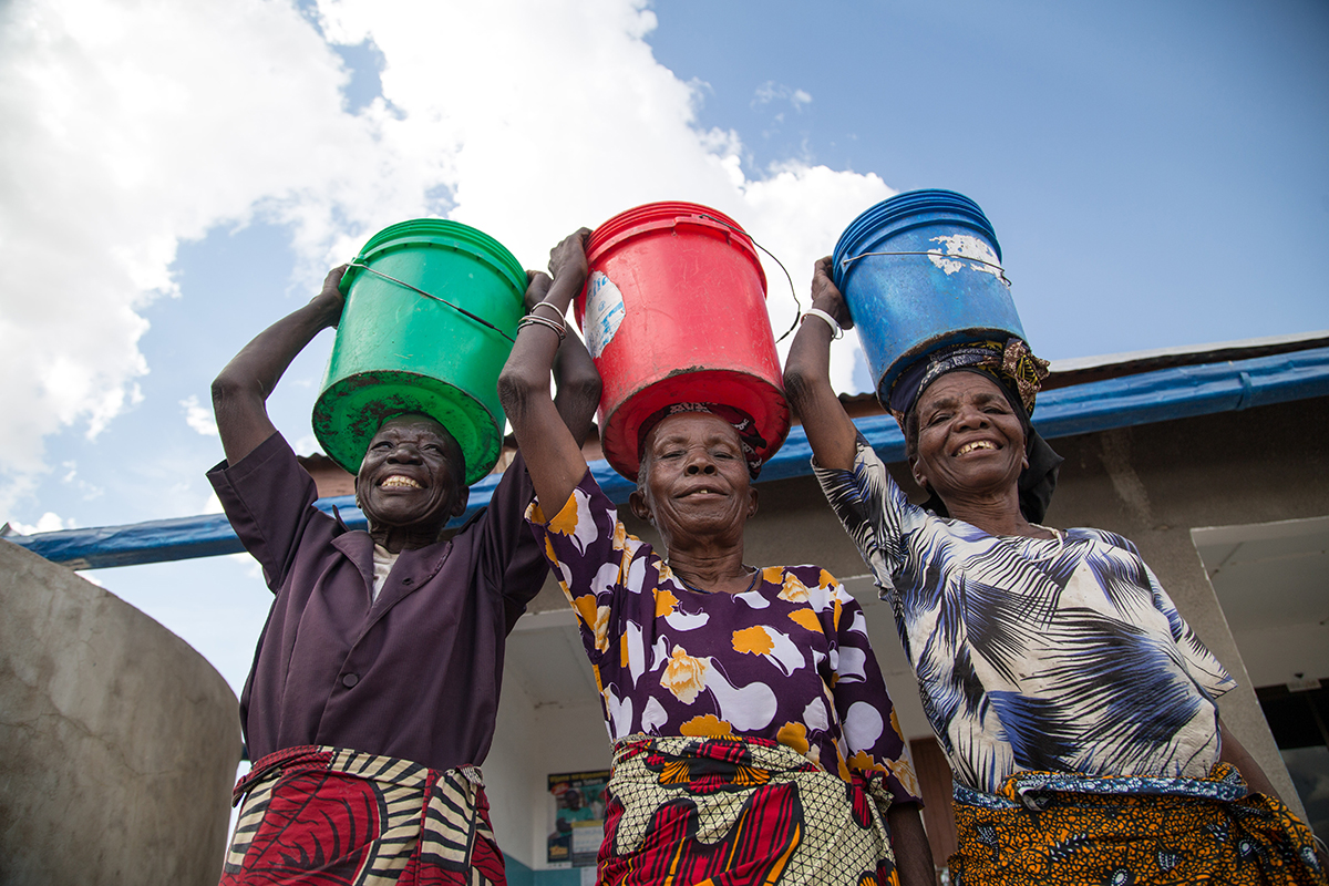 Three women stand smiling with buckets of clean water on their heads.