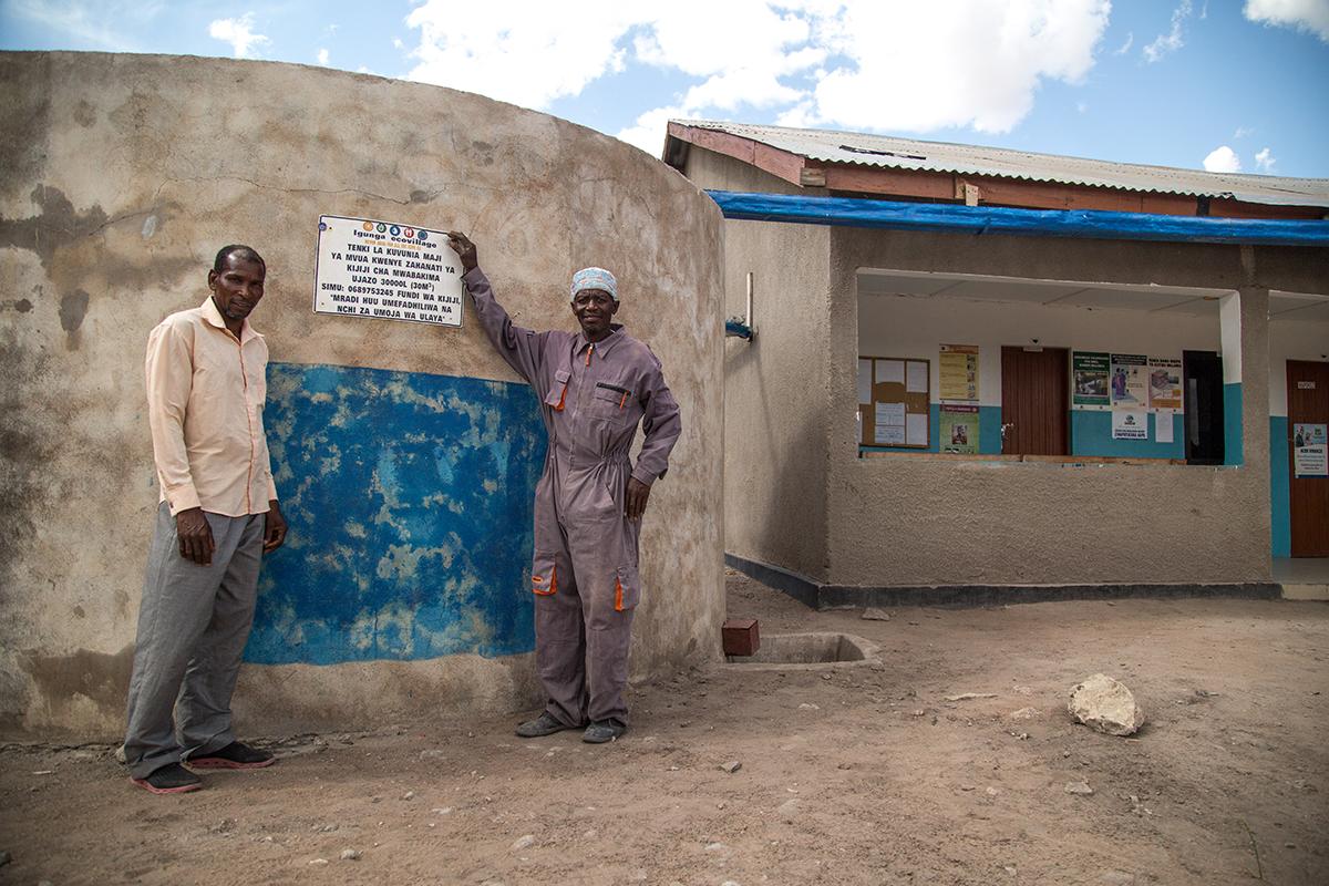 Two men proudly display their village rainwater harvesting tank.