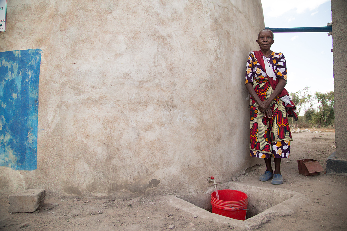 A woman stands waiting while water pours from the dispensary's rainwater harvesting tank into a bucket.