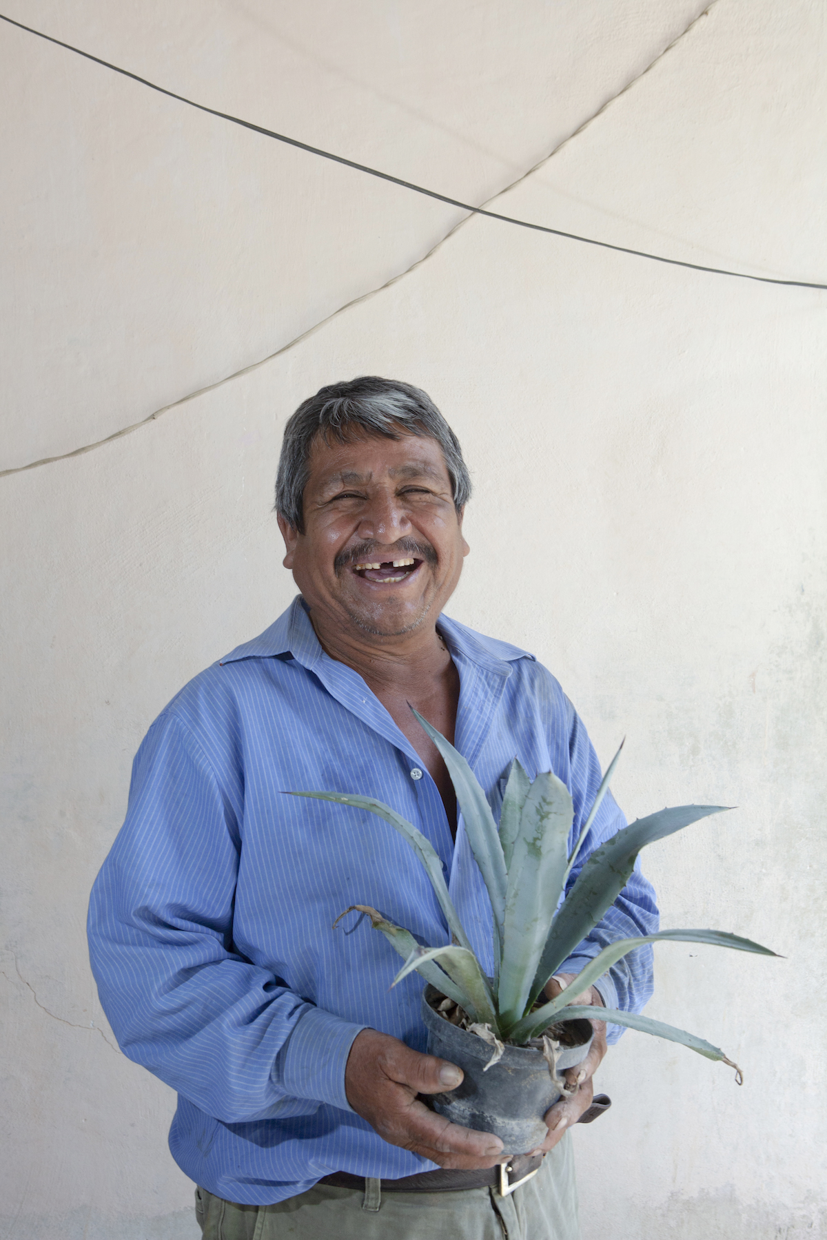 Ciro Rodriguez Cruz holds an agave plant in his home in Santa Ana del Rio. Photo by Russ Powell.