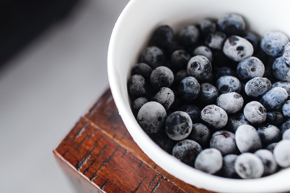 A bowl of frozen blueberries.