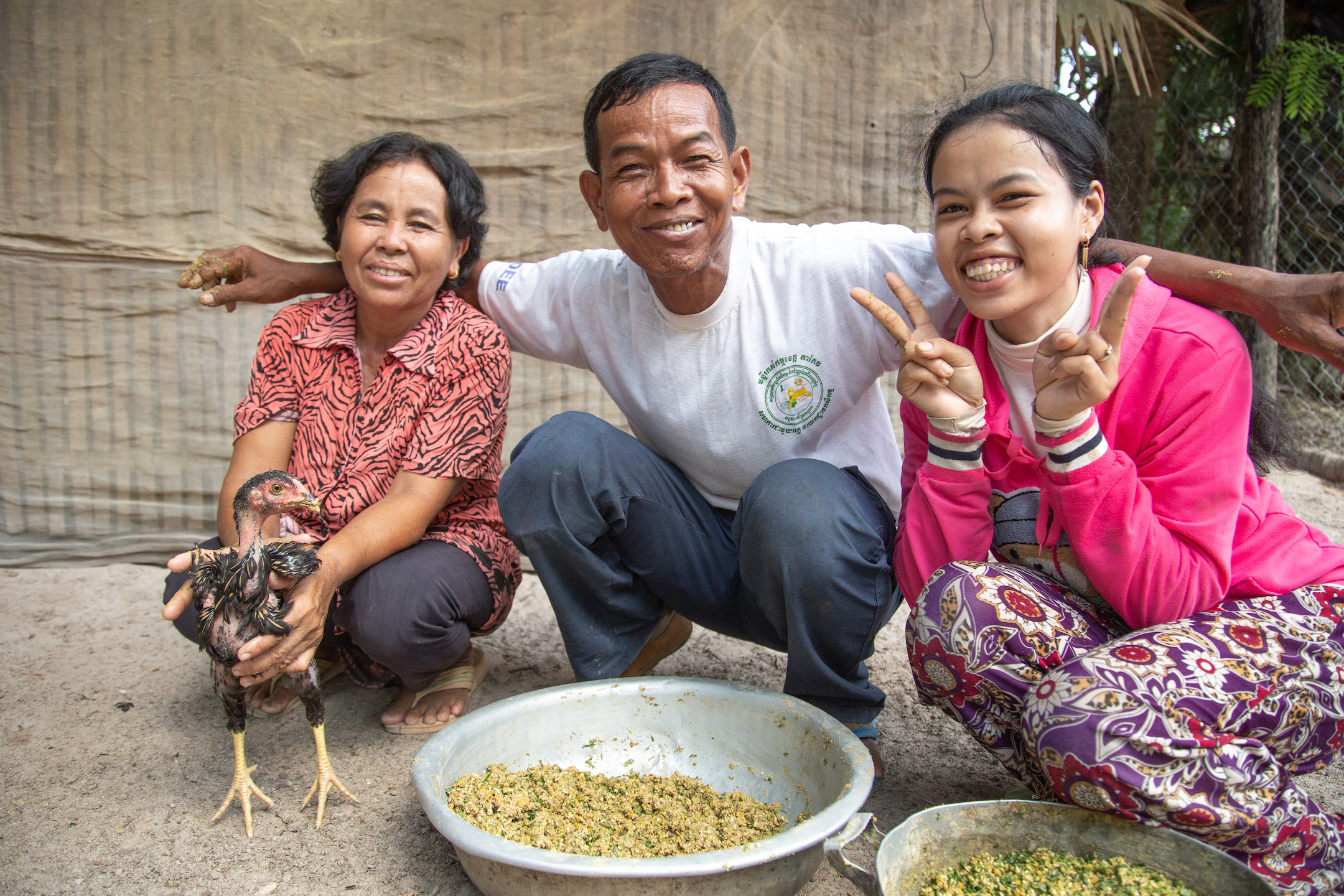 Mao Neng, her husband Prak Bon and their daughter Brak Syenech sit together smiling with a small chicken.