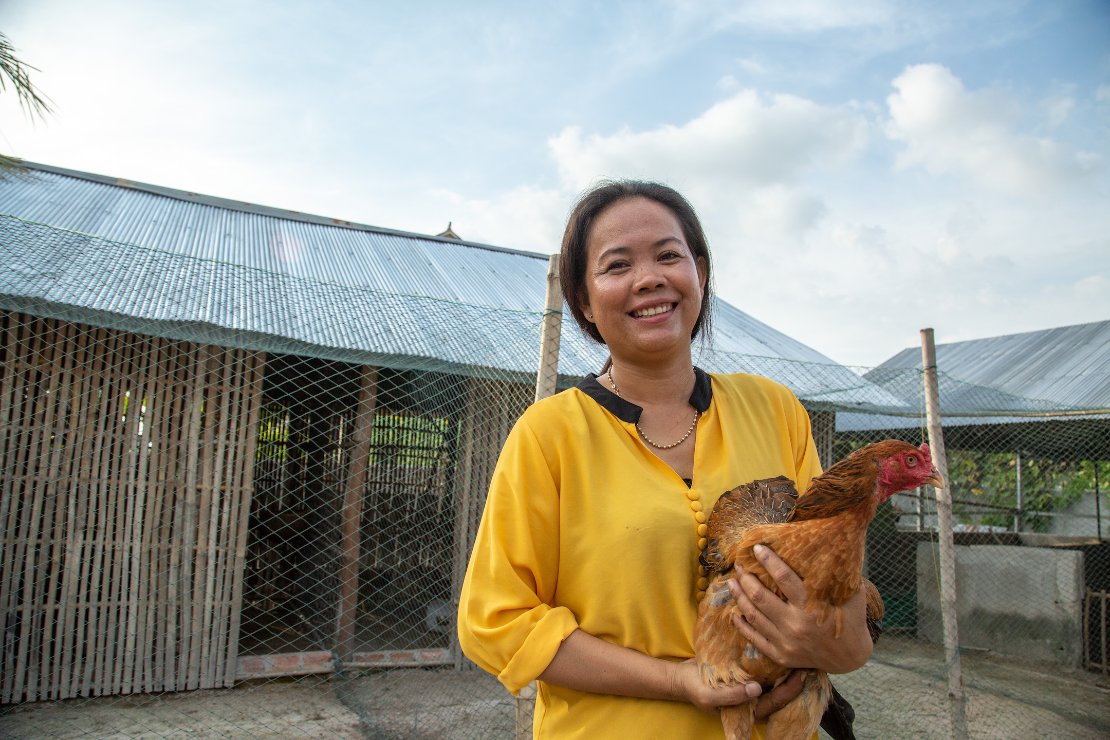 Hoy Lin smiles while she holds a chicken.