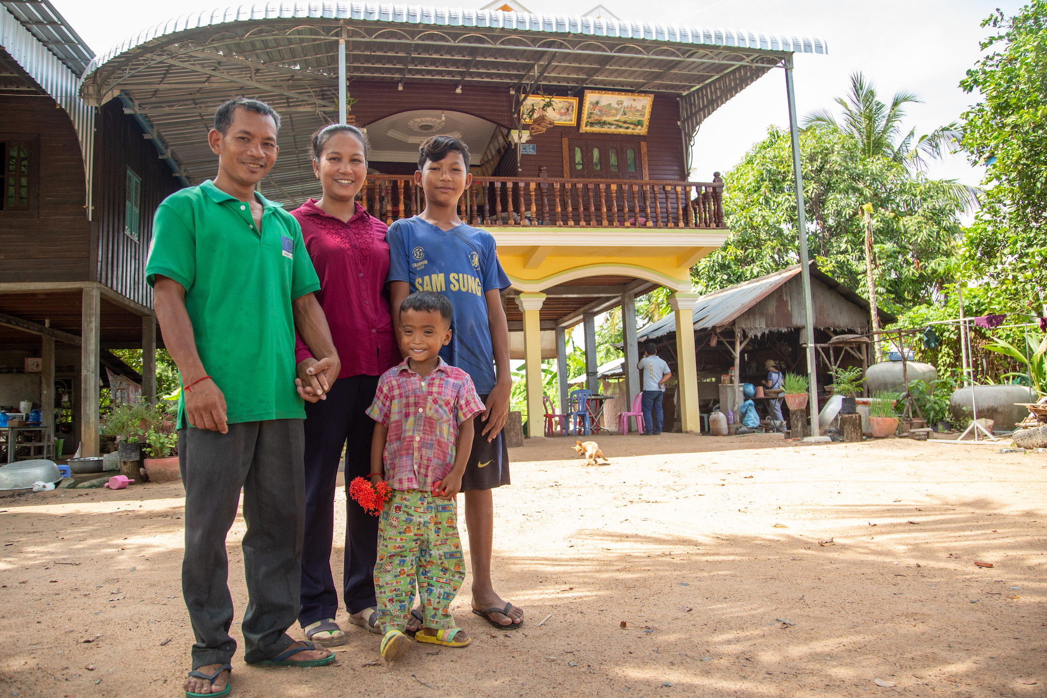 Rith Chantha, her husband, Sun Sitaol, and their two children stand smiling in front of their new home.