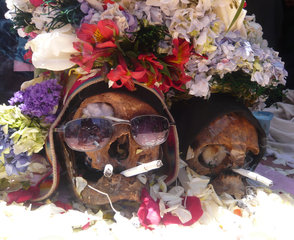 Two skulls adorned in flowers sit on the ground with lit cigarettes in their mouths.