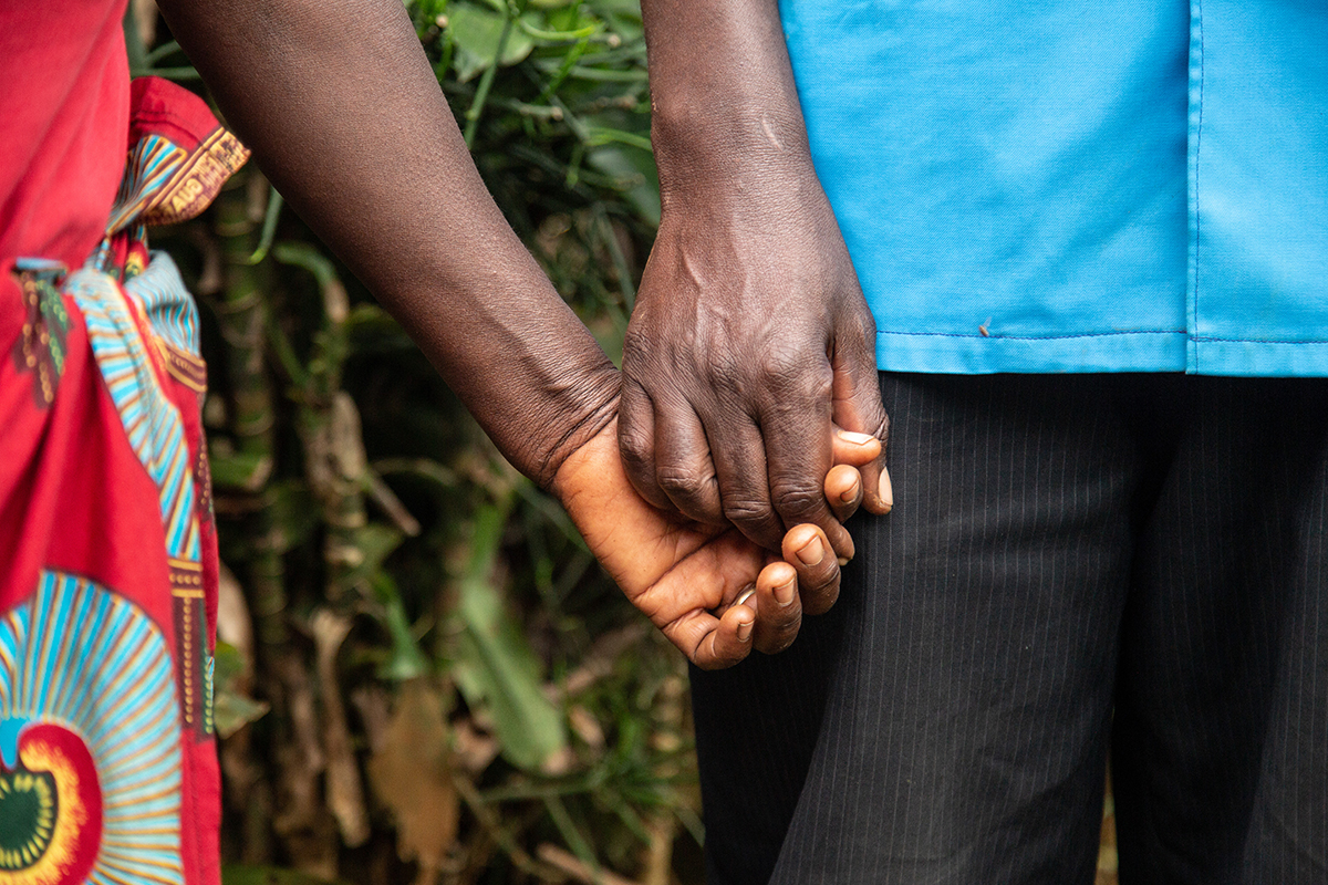 A close up of a man and a woman holding hands.