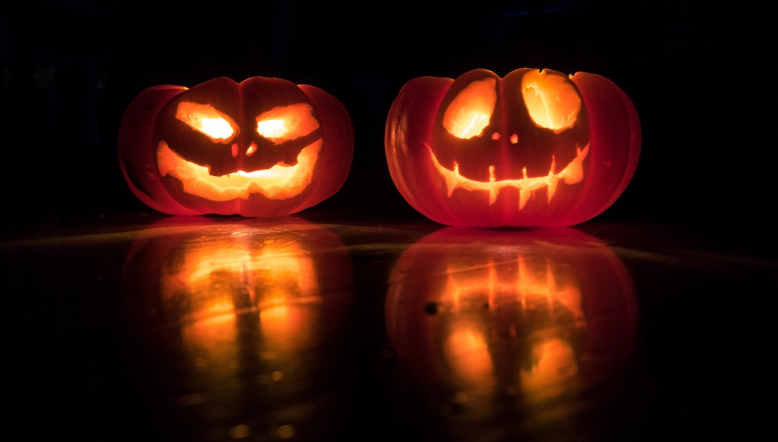 Two smiling jack-o'-lanterns sit glowing on a dark background.