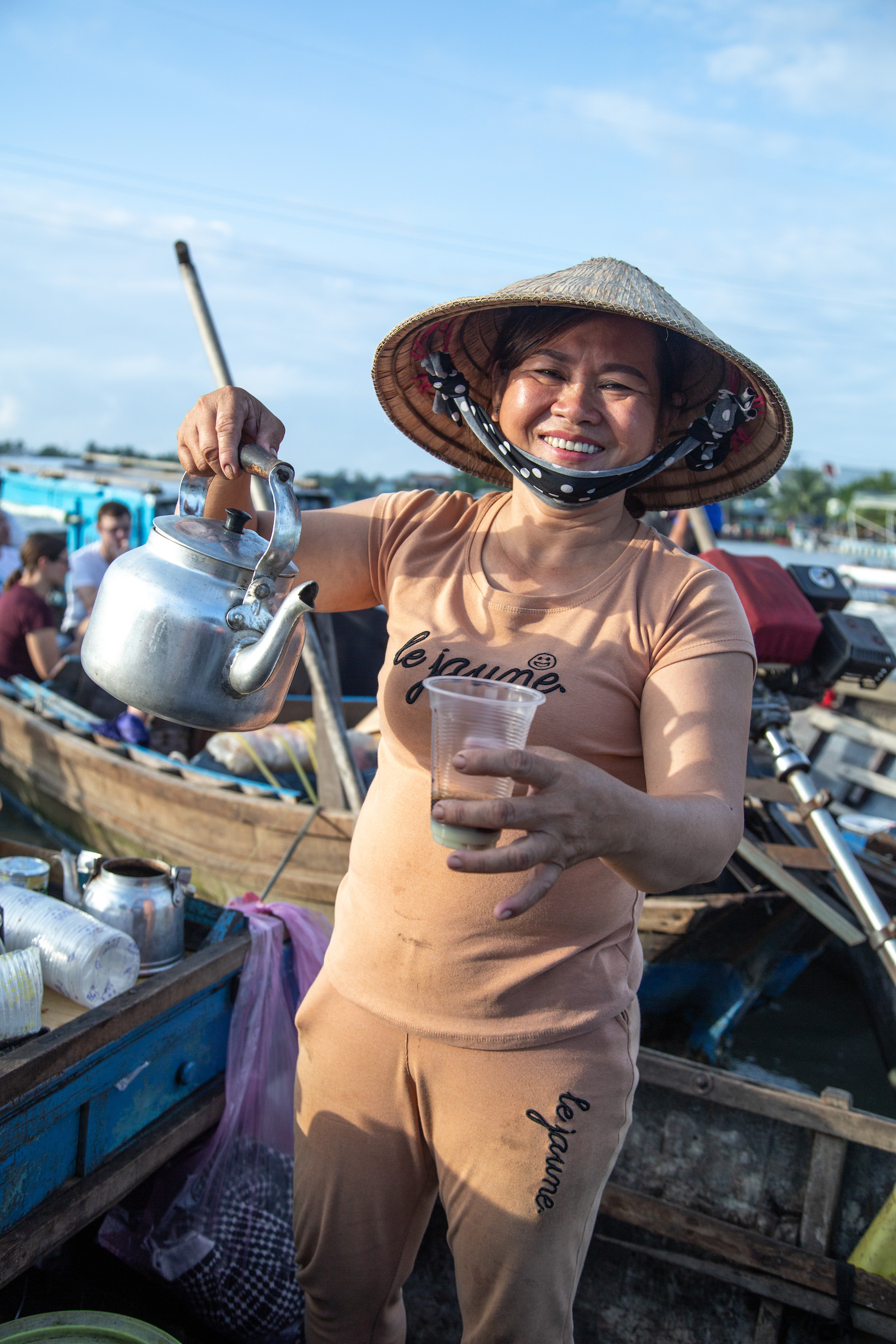 A woman smiles while holding a kettle and a cup of coffee near her boat storefront.