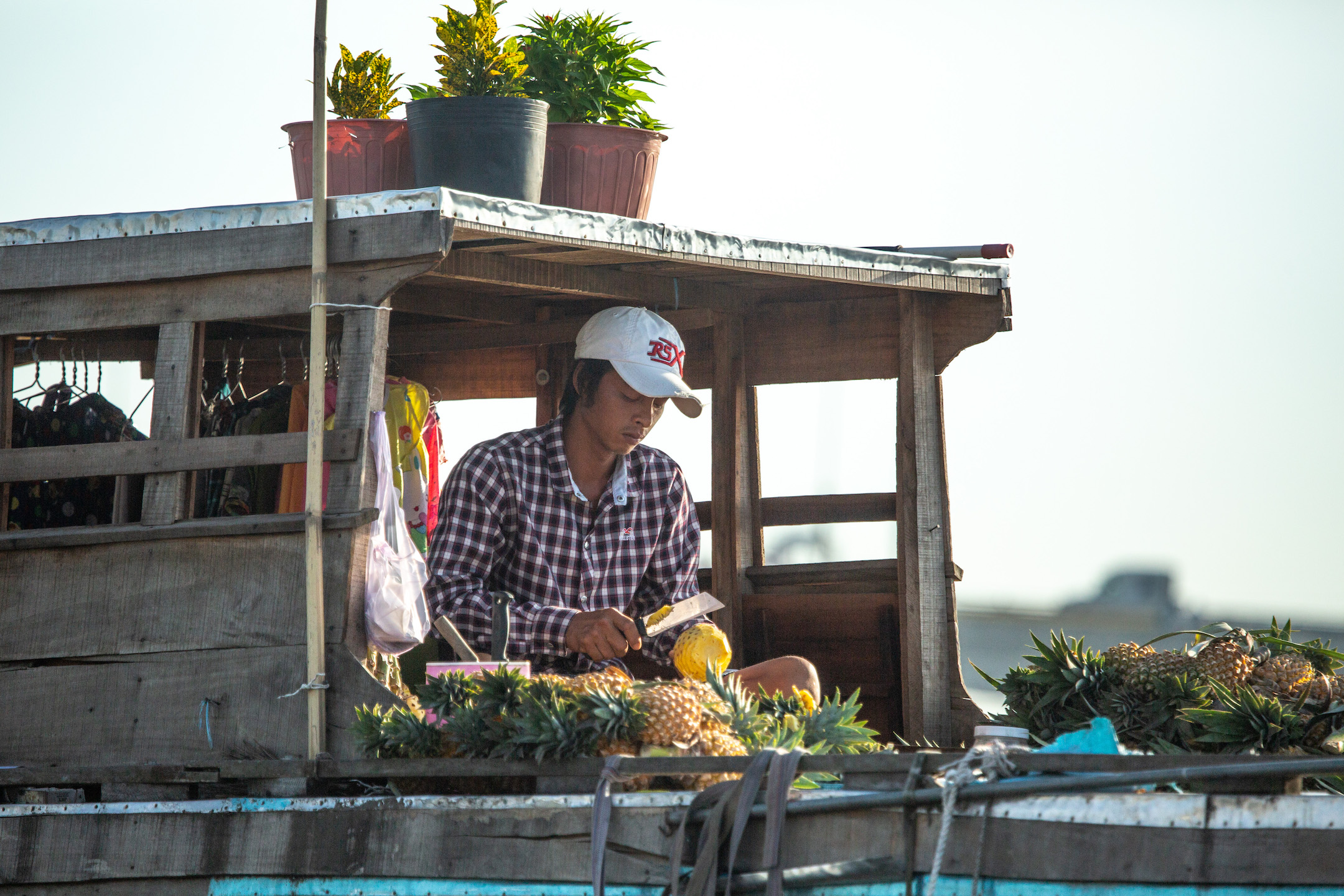 A young man chops fresh pinapple at a booth.