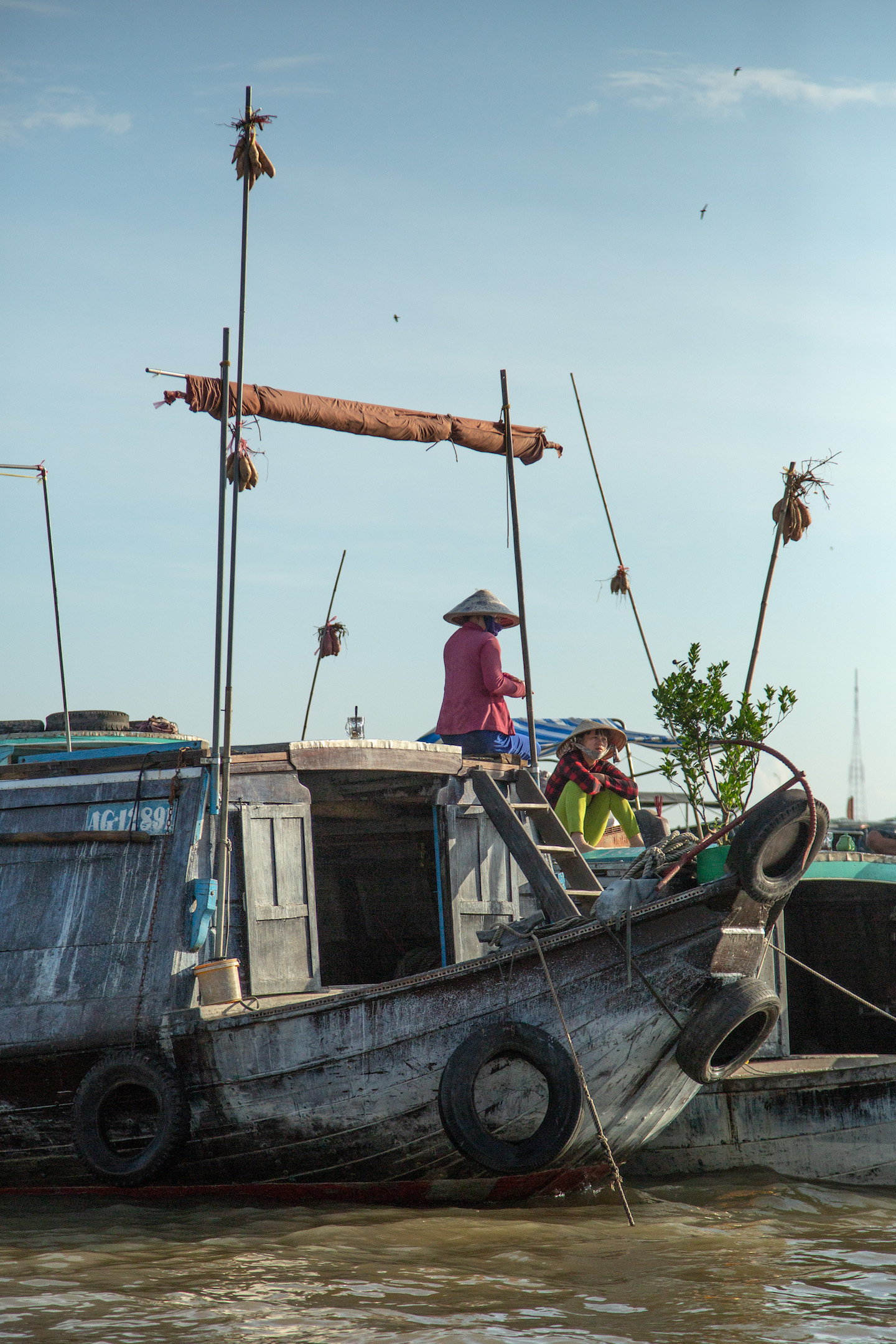 Vendors display their goods atop tall bamboo poles on their boats.