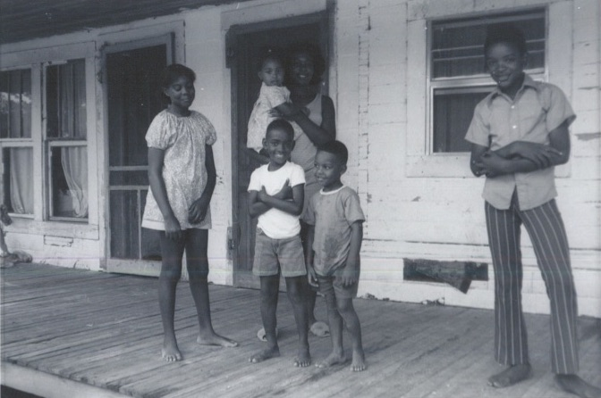 A family involved in the Heifer/Prentiss Institute project in front of their home