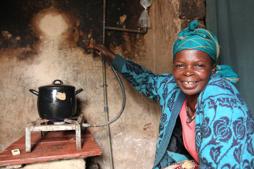Donata Musanabera lights a gas burner powered by biogas produced from cow manure.
