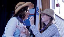 Principal Dixie Herbst Kisses a Pig