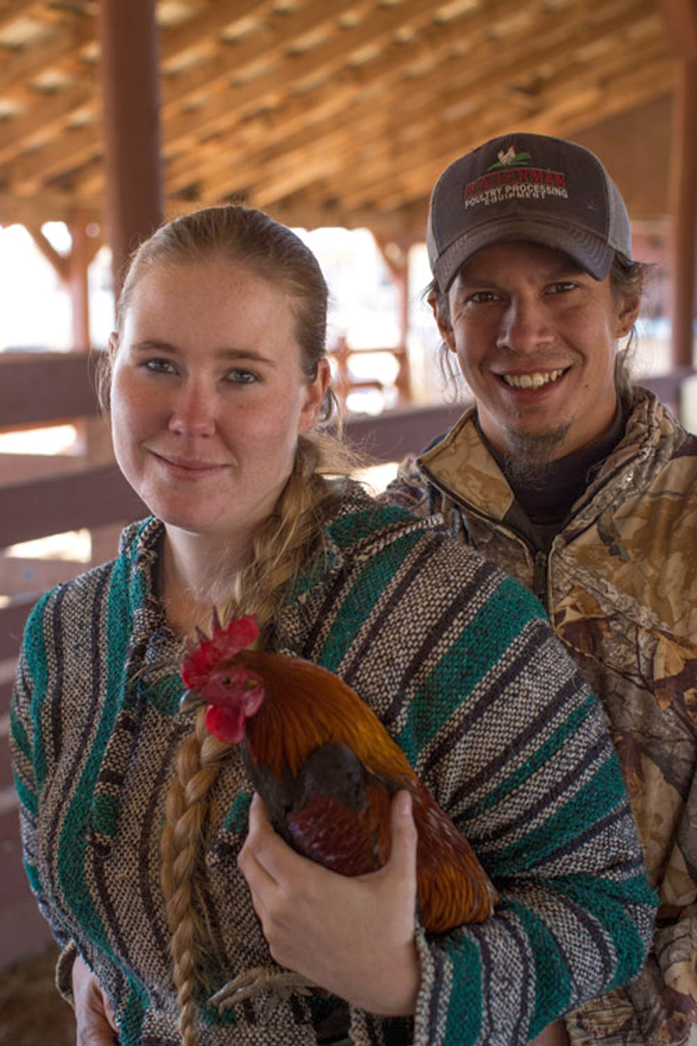 Woman and man hold a rooster