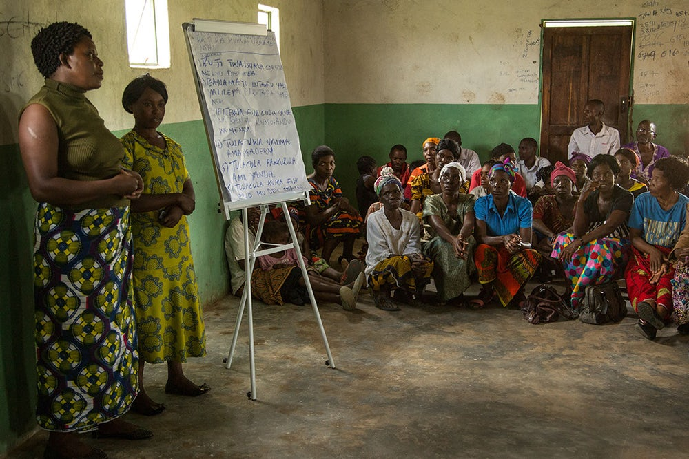 Two women in a building in Zambia present to a group of adults.
